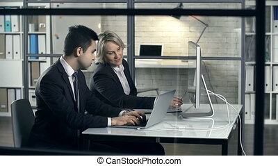 Side view of two colleagues discussing project details using computer and laptop
