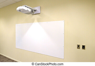 Projection screen with video image projector hung on a wall...