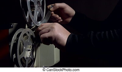 Projectionist operates a vintage 16 mm movie projector