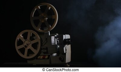 Projector displays movies in the smoke. Black background