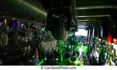 projector turning around in nightclub with many dancing people