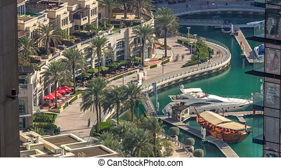 Promenade and canal in Dubai Marina timelapse with boats around, United Arab Emirates