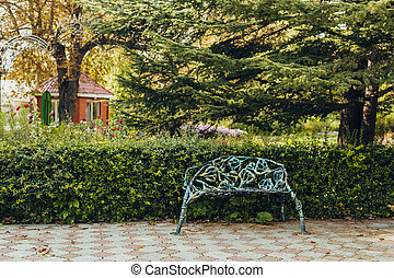 Promenade in a beautiful city park with a bench