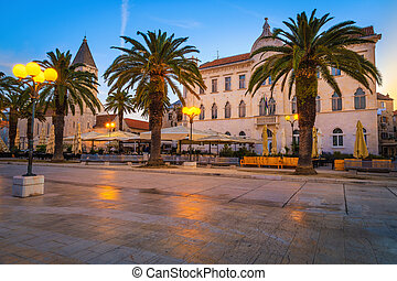 Promenade with street cafes and palm trees at dawn, Trogir