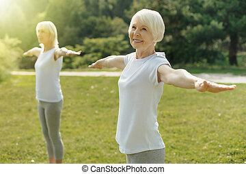 promieniejący, emerytowany, kobieta stanie, z, jej, herb outstretched