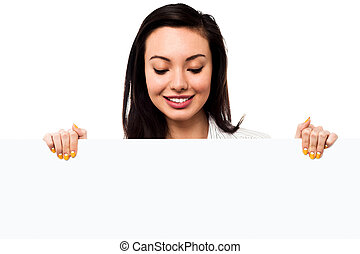 Pretty young girl holding blank banner ad, business concept
