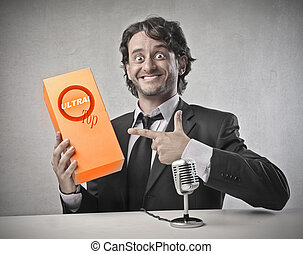 businessman promotes product sitting at the table with microphone