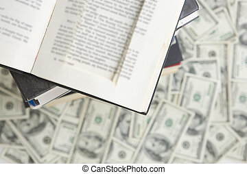 Books on top of one hundred dollar bills with prop book on top to hide money