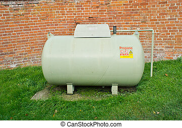 Propane tank - A large propane tank against a red brick wall