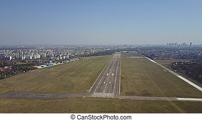 Propeller airplane taking off from airport runway on a sunny day, aerial shot