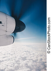 Propeller plane in air above the clouds