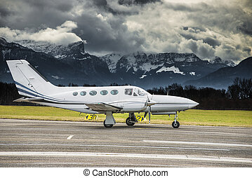 Propeller plane parked at the airport. Mountain airport. Airport in front of high mountains.
