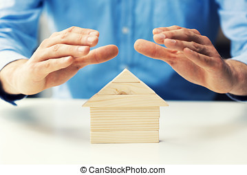 property insurance concept man protect model of the wooden house