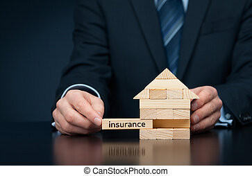 Property (family house) insurance protection concept. Insurance agent complete wooden model of the house with last piece with text insurance.