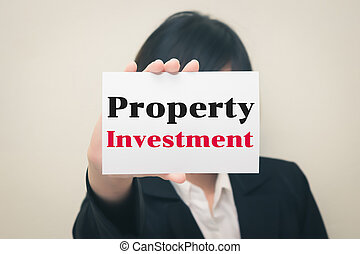 Property Investment, message on the card Held by women.