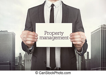 Property management on paper what businessman is holding on...