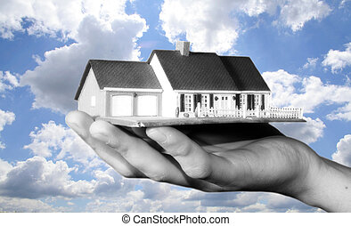 property market - a young businessman is holding a house in ...