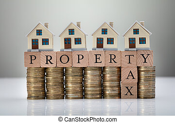 Property Tax Concept With Stack Of Coins And House Models