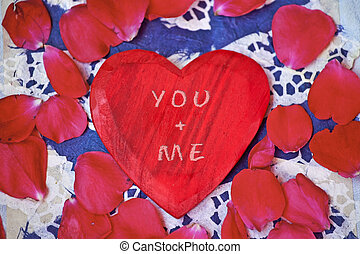 a red wooden heart with rose petals and an inscription for a marriage proposal