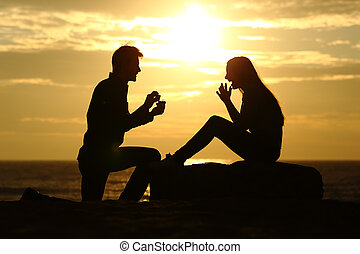 Proposal on the beach with a man asking for marry at sunset...