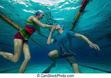 Guy proposing to his fiancée in unusual special pool underwater way