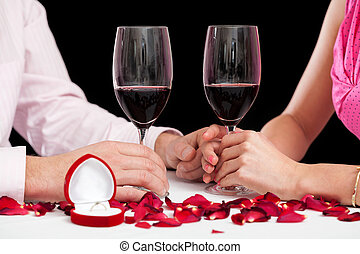 A closeup of glasses filled with red wine on a proposal evening