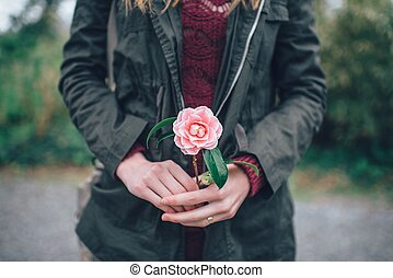 young girl holding a flower in her hands