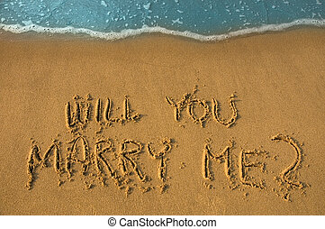 proposition - will you marry me written in sand, cyan water