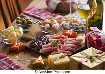 Full table of prosciutto, olives, cheese, salad and wine for holidays