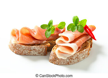 Prosciutto open faced sandwiches garnished with red chili peppers