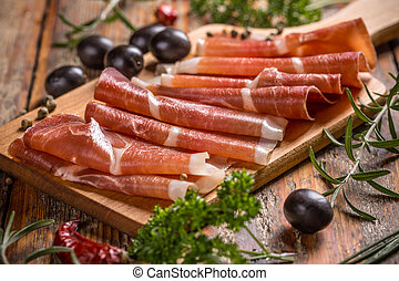 Thin slices of prosciutto with olives on wooden cutting board