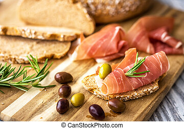 Prosciutto with olives on wooden background
