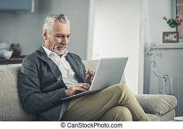 Prosperous experienced businessman working on laptop