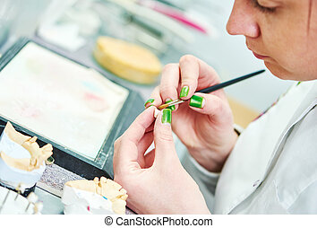 prosthetic dentistry process - Dental technician painting...