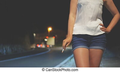 Prostitute with cigarette waiting for the client at night...