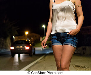 Prostitute with cigarette waiting for the client at night street.
