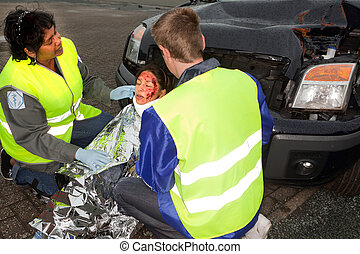 Protecting blanket for injured woman - Two paramedics...