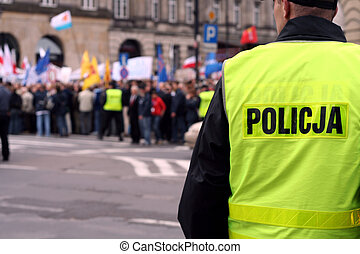Police officer talking on a radio protecting an anti-government demonstration in Warsaw Poland on 7 October 2006 (Blue March by Platforma Obywatelska). Purposely taken with a shallow DOF not to detail faces.