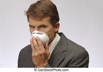 Protection from flue, H1N1 - Businessman holds mask on face.