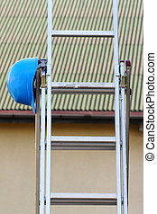 Protective blue helmet on aluminum ladder, safety at work