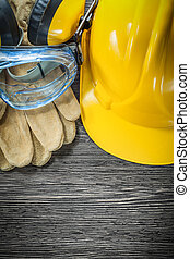 Protective gloves goggles earmuffs hard hat on wooden board