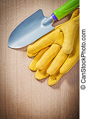 Protective gloves hand spade on wood board gardening concept