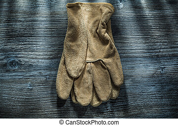 Protective gloves on wooden board.