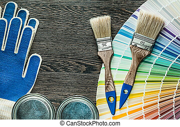 Protective gloves paint brushes cans pantone fan on wooden board