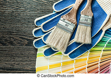 Protective gloves paint brushes pantone fan on wooden board