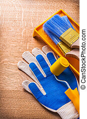Protective gloves paint roller tray and brushes on wooden board