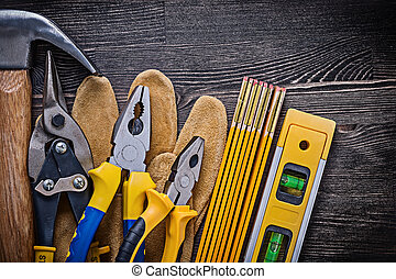 Protective gloves pliers tin snips wooden meter construction level hammer.