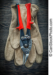 Protective gloves steel cutter on wooden board.