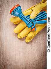 Protective gloves with water spray nozzle on wood board gardenin