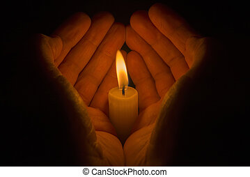 Protective hands around a burning candle